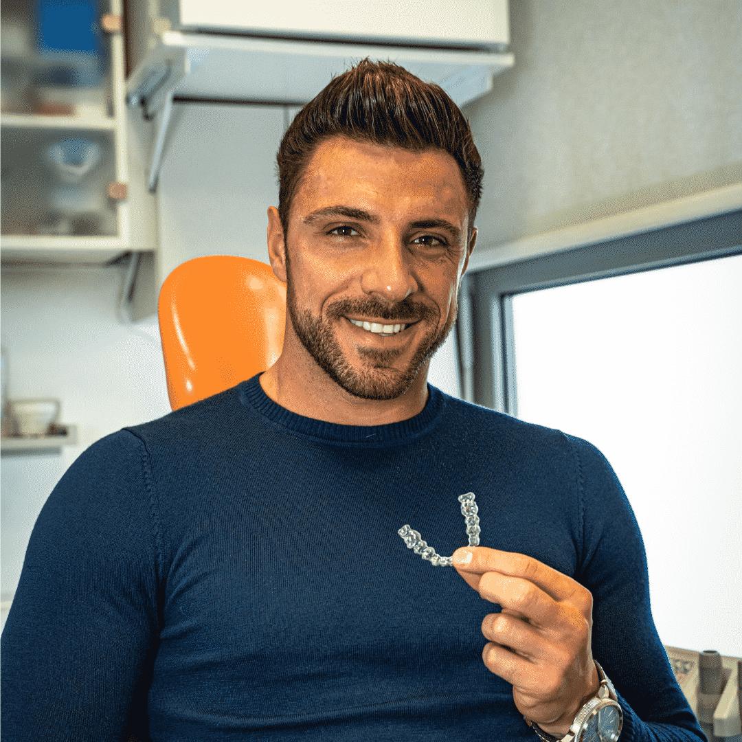 OrthoDental - Gregor Čeglaj v roki drži Invisalign zobni aparat in se smeji