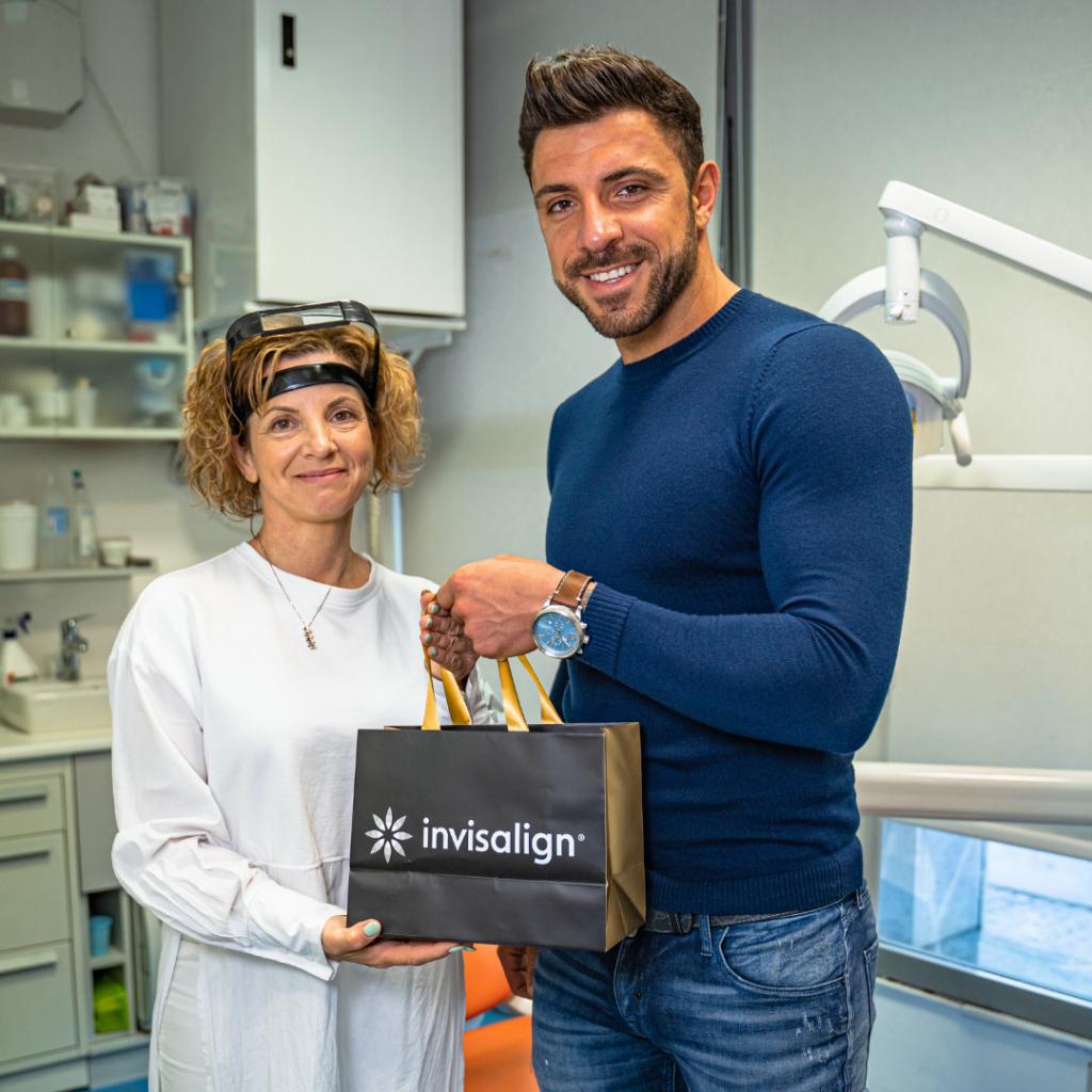 OrthoDental - Gregor Čeglaj v roki drži vrečko Invisalign, ob njem stoji Gordana